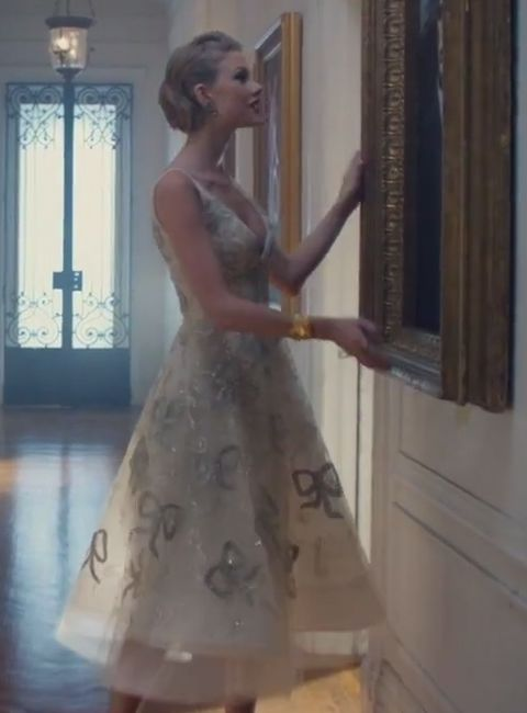 Taylor Swift's Blank Space Outfits.she looks picture-perfect while hanging her finished portrait in the hallway in a tea-length Oscar de la Renta dress with metallic bows on it.