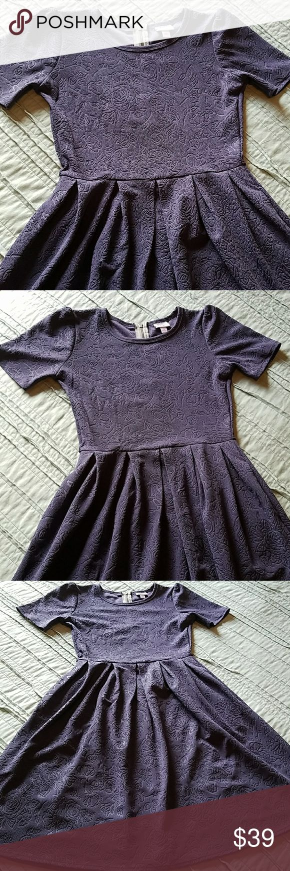 Lularoe Amelia Rose Embossed Dress in Purple This is a gorgeous Amelia in fantastic condition!  Only worn a few times so grab this up at a discount!  Dress has a gorgeous pleated design and the rose design is embossed as part of the fabric.  I wish I could keep this dress, but it is just too small for me.  Don't forget it has pockets! 😍😍😍 LuLaRoe Dresses