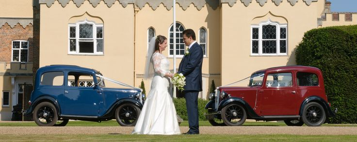 Bride and groom with two vintage wedding cars at Buckinghamshire bridal venue Hampden House near Great Hampden.