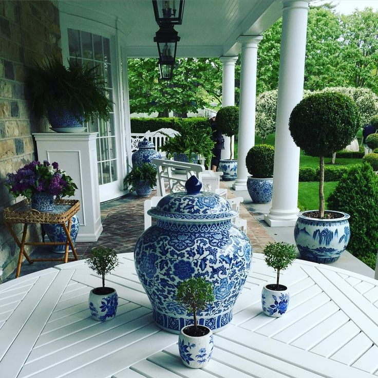 Blue and white theme on porch - pots of tiny topiaries, boxwood & fern - Carolyn Roehm