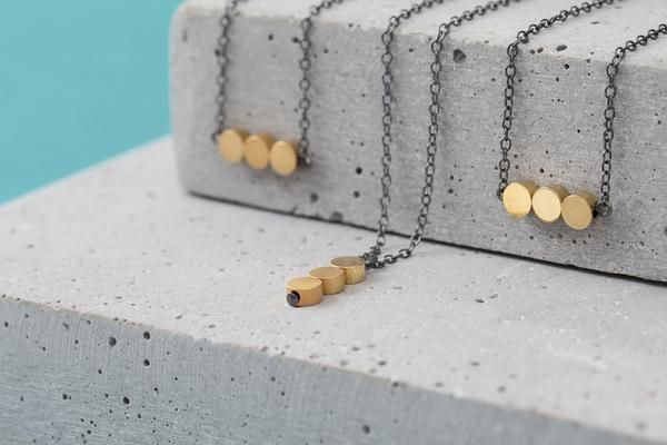 Oxidized silver necklace with three dainty circle beads plated with 16k shiny gold. The necklace has a minimal and timeless design, yet stands out with the contrasts between dark silver and shiny gold.