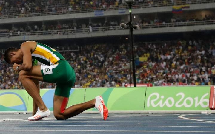 Wayde Van Niekerk kneels with his head in his hands after claiming a new world record in the 400m final