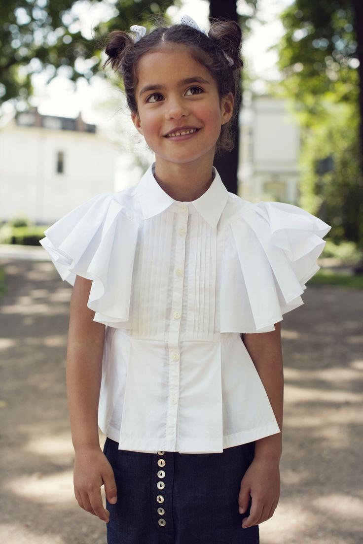 Witte blouse van Jottum. De blouse heeft een knoopsluiting, vlindermouwen en aan de onderkant zit een strook met plooien.