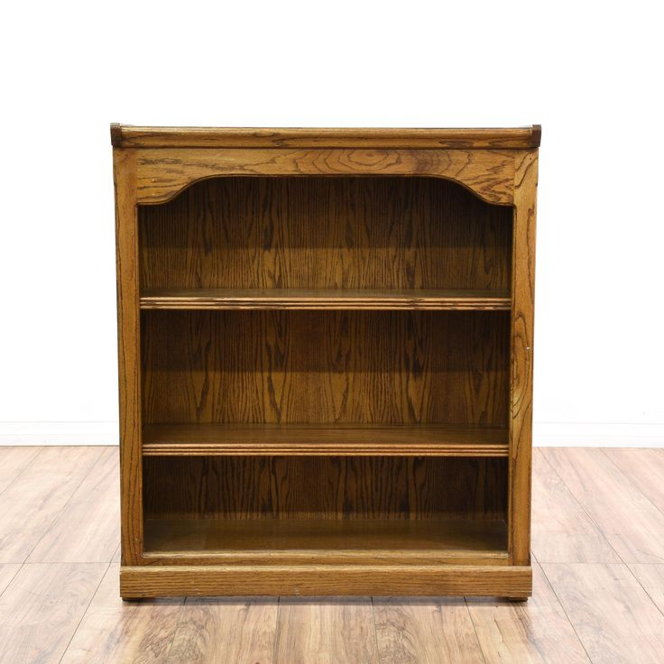 This traditional bookcase is featured in a solid wood with a light glossy oak finish. This low bookshelf has 2 shelf tiers, fluted trim and curved top edges. Great for displaying books and magazines! #americantraditional #storage #bookcase&shelving #sandiegovintage #vintagefurniture