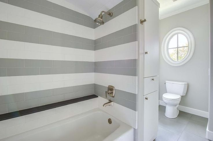 Beautiful bathroom features a drop-in shower fitted with white and gray subway tiles alongside a ...