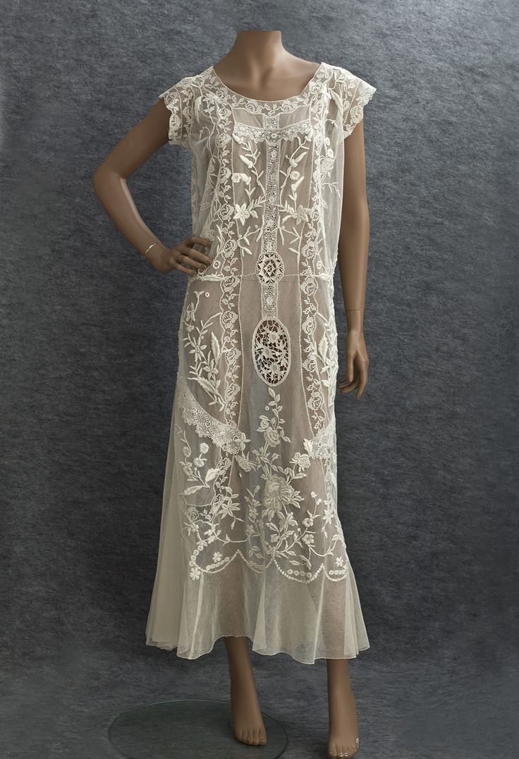 Embroidered mixed lace tea dress, c.1922. High relief hand embroidery & handmade lace on a ground of ivory cotton tulle, with inset panels of delicate flat filet lace, textured Irish crochet lace and Venetian needle lace medallions. The straight silhouette is softened with bias-cut hem flounces and side-back panels. Loose fitting, it slips on without closures, and is sheer so will need a slip. Pinned by #Blucha from vintagetextile.com