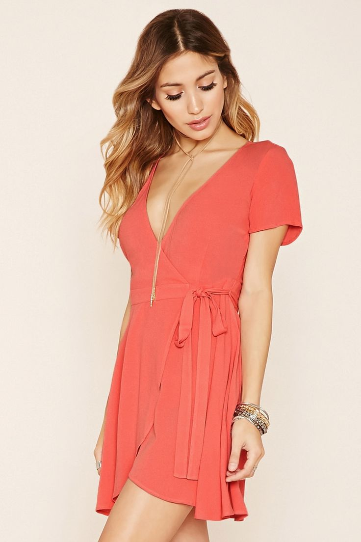 A chiffon wrap dress featuring a plunging surplice neckline, self-tie waist and short sleeves.
