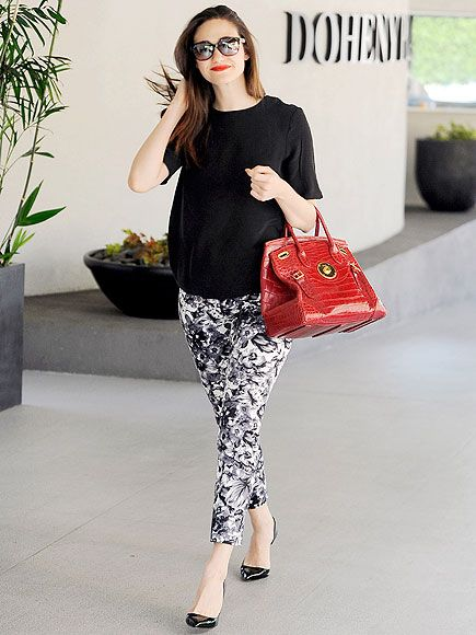 Emmy Rossum gives a black-and-white outfit a pop of color with a red crocodile bag while out Thursday in West Hollywood.