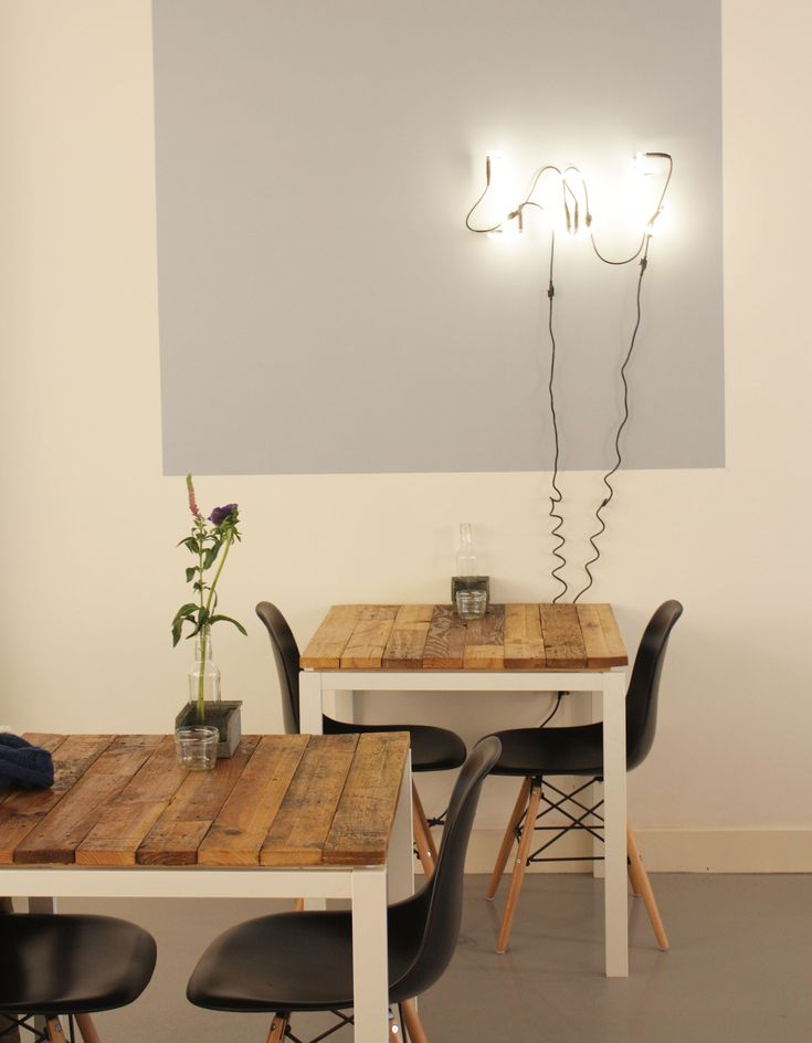 Lunchroom Lot in Den Haag | scrap wooden tables with black dsw eames chairs | neon light on the wall | concrete floor