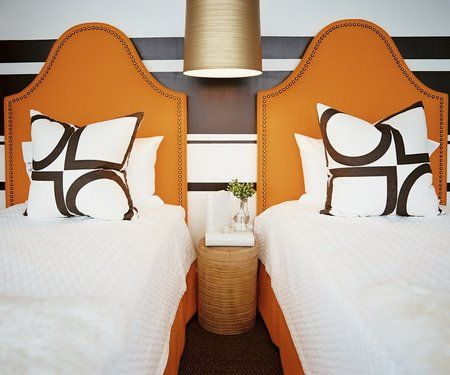 Neutral color scheme in this eclectic bedroom- browns, tans and whites with a pop of rustic orange on the headboards and bedskirts.  Love the stripes on the wall, high headboards with brass nail heads, metallic pendant light and the geometric shapes on the pillows.
