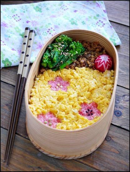 posted by @ahiru_bento 桜の季節がもうすぐそこに♪春のそぼろ弁当です。玉子と鶏そぼろ、葉の花の胡麻和えなど。#obentoart #bento #わっぱ #お花見