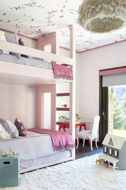 Adorable pink girl's room features a white feather chandelier is hung from  a pink butterfly wallpapered