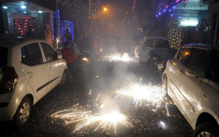 Indian people lighting firecrackers on a street littered with spent crackers during the Diwali festival celebrations near New Delhi, India