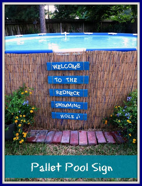 Natural Reed Fencing and cute palette signs around an above ground pool (Natural Reed Fencing found in Lowes).