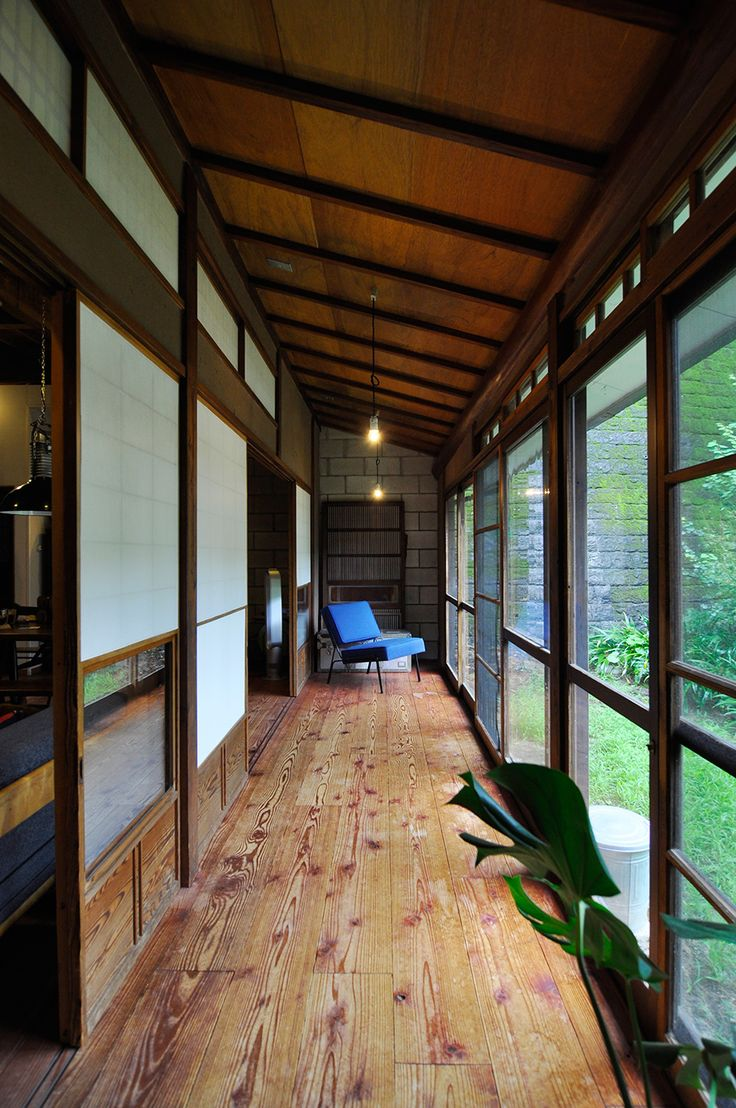 柿渋を塗った杉板の床。長い縁側の奥にはピエール・ガリッシュのソファ。青い色が和の空間に映える。