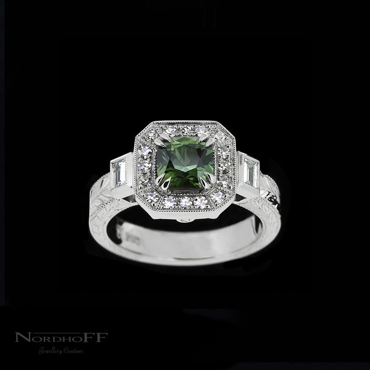 In the centre is a stunning custom cut Forrest green Australian Sapphire, surrounded by a halo of vintage inspired single cut diamonds. Bezel set baguette diamonds lead to a beautifully hand engraved band. From start to finish this ring is completely handmade in the traditional way, and really hits that vintage 'Gatsby' feel.