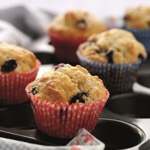 Blueberry muffins in red and blue muffin cases on a baking tray-healthy