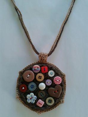 Colar feito em crochê com linha e barbante nas cores marrom e bege e botões de diferentes formas, cores e tamanhos bordados com linhas de diferentes cores. A altura do colar é regulável.