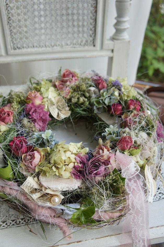 auf einem mit wiesenkr utern und reben umbundenen kranz finden sich getrockneten rosen. Black Bedroom Furniture Sets. Home Design Ideas