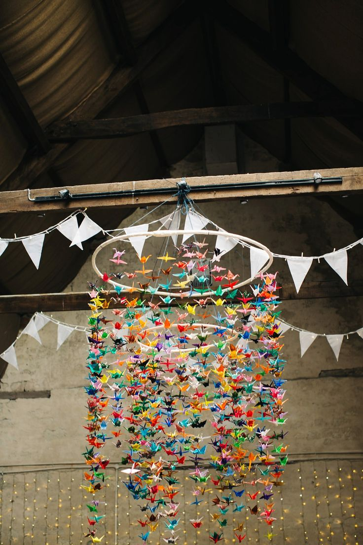Colourful paper crane chandelier from a rustic Dorset barn wedding with paper cranes. Photography by Richard Skins.