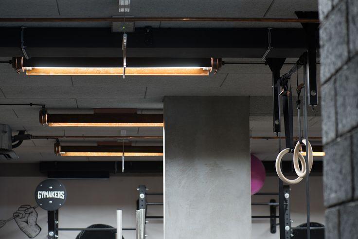 Oświetlenie LED dostarczone przez HSK LEDY dla studio Gymakers w Krakowie. Customowe, wystarzane rdzą oprawy w starym stylu, neon oraz wielkie miedziane litery z żarówkami LED są ukoronowaniem postindustialnego wystroju wnętrz tej siłowni.      Custon LED lighting provided by HSK LEDY for Gymakers studio in Krakow. Custom old-school rusted fixtures, neons and large copper letters with LED bulbs are the culmination of the postindustrial interior design of this gym.    fot. Przemek Szuba