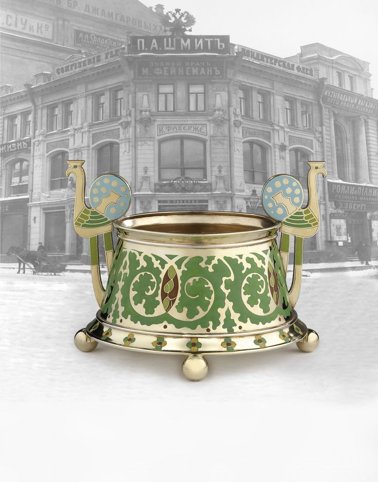 of tapering circular form decorated with undulating swirls of champlevé green enamel foliage and stylised cloisonné enamelled green and brown cones, the flared base enamelled with champleve quatrefoil flowers, supported on four ball feet, the handles enamelled in the form of peacocks, shown against an image of Fabergé's Moscow shop. Moscow, circa 1905, inventory number: 18925. 15.7 cm diameter to base.