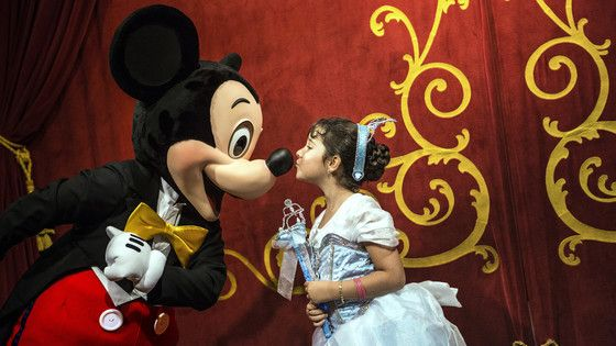 A young female Guest dressed up as an enchanting Disney Princess kisses Mickey Mouse on the nose