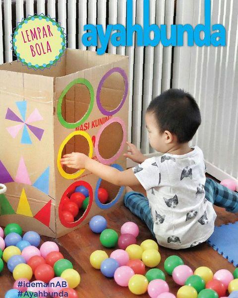 "Ajak #balita Anda menjadi lebih kreatif dengan #idemainAB ""LEMPAR BOLA"" seperti di foto ini.   Yang #ayah dan #bunda butuhkan hanya kardus bekas, spidol atau kertas untuk memberi warna, gunting dan bola beraneka warna.   Ajak #balita Anda menyesuaikan warna bola dengan lubang warna. Si kecil pasti senang belajar warna sambil melempar bola. Selain mengenal warna, kemampuan motorik kasarnya pun terasah."