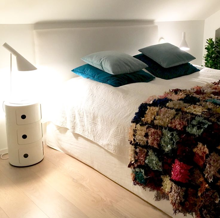 Bedroom with marocain rug on bed. AJ lamps, kartell side tables