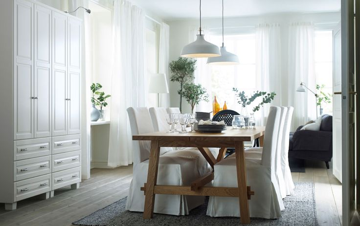 A light dining room with an oak table that seats eight people. And six dining chairs with white long chair covers.