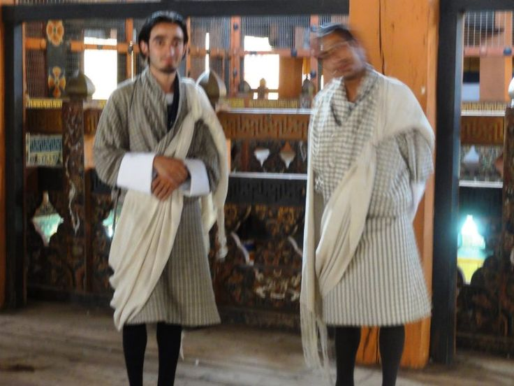 """W urzędach i miejscach kultu religijnego Bhutańczycy mają obowiązek ubierać się w tradycyjne stroje. Mężczyźni noszą """"go"""", podkolanówki i pełne buty, a dodatkowo wymyślnie zawiązują szarfę-szal. Po jego kolorze można poznać do jakiej grupy społecznej należy jego właściciel."""