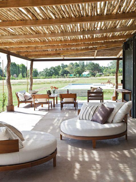 Galería con techo de madera rústica en una casa de fin de semana. Sillones redondos de lapacho con almohadones de tusor rayado le dan un toque súper confortable a este exterior.