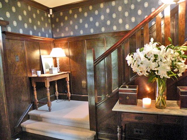 Wallpaper adds interest and sparkle to a dark hallway.  By Room Service Interiors.