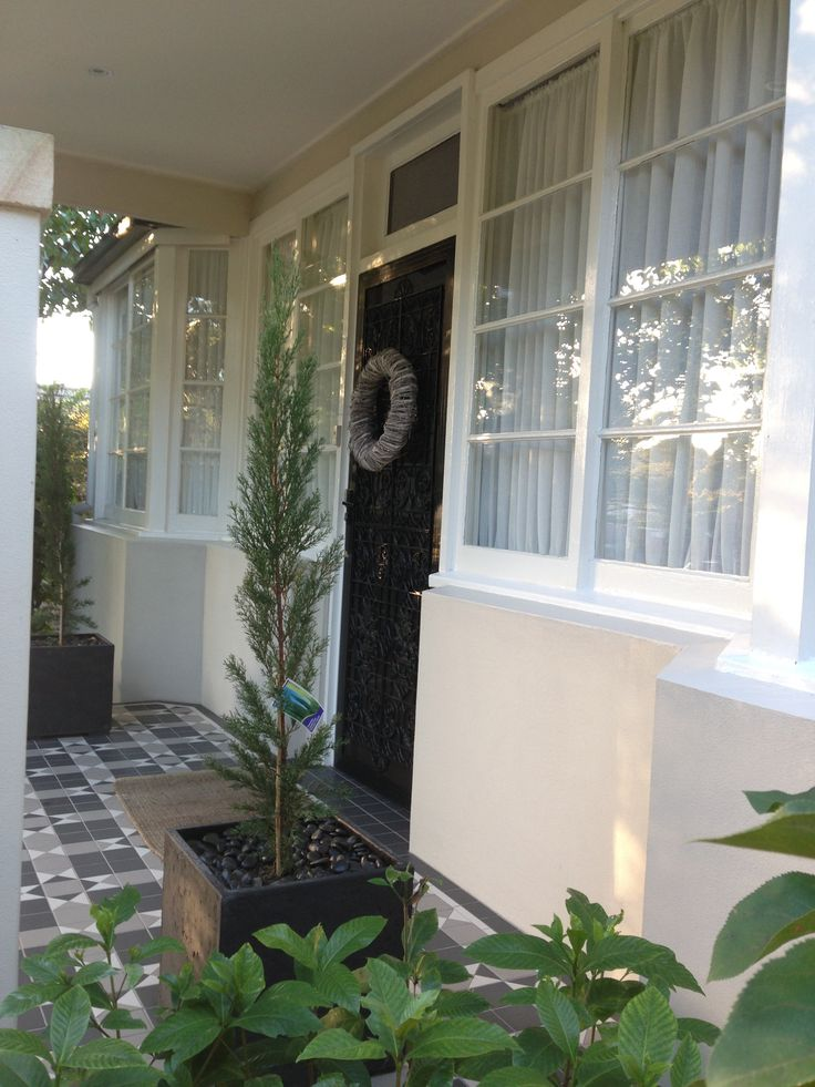 Front porch with two potted pencil pine shrubs. A little bit of France by the front door.