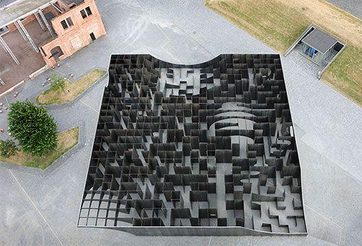 C-MINE LABYRINT  Tien jaar geleden kreeg de oude mijnsite van Winterslag een nieuwe bestemming: C-Mine. Om die verjaardag extra in de verf te zetten liet de stad Genk een opmerkelijke constructie bouwen: een gigantisch labyrint bestaande uit stalen platen van vijf meter hoog. Goed voor een gezonde zondagse wandeling!  Het 'experimentele' labyrint zoals de jonge kunstenaars-architecten Pieterjan Gijs en Arnout Van Vaerenbergh het noemen, weegt in totaal b