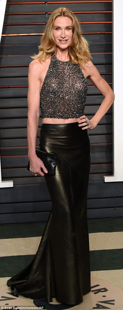 Sheer: Actress Kelly Lynch flashed her midriff in a sparkling halter neck top and long lea...