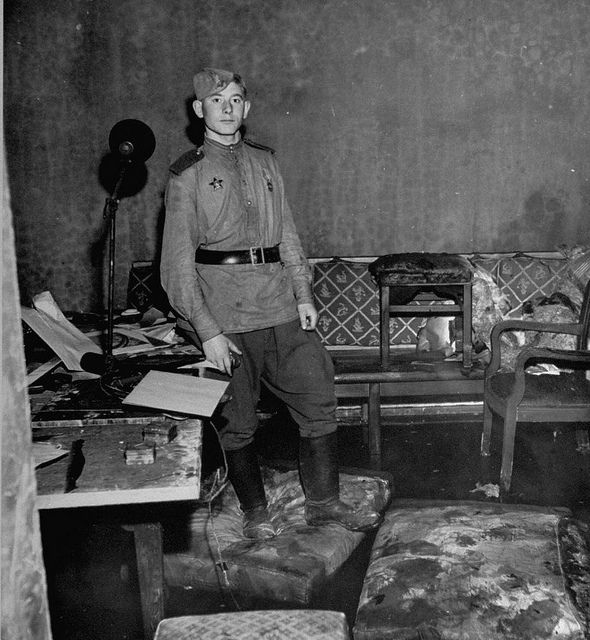 1945 Russian soldier standing amid rubble in Hitler's command bunker:
