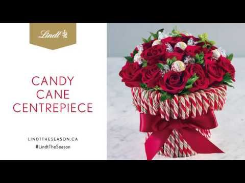 Company coming? Easily make an impressive centrepiece. Glue candy canes to the outside of a cylindrical vase, fill with  roses and tuck wrapped Lindt chocolates in with the flowers. #LindtTheSeason