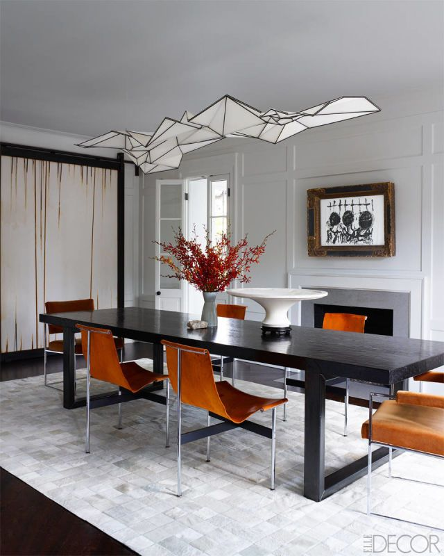 Burnt orange seating adds color & depth to the quiet dining room // by Darryl Carter