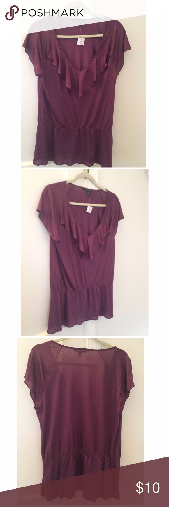 """NWT Banana Republic Purple Short Sleeve Top Large New, with tag, Banana Republic short sleeve top w/ feminine ruffled V-neckline and elasticized drop waist w/ flutter hemline. The color is a beautiful rich grape hue (purple). Material is 70% rayon & 30% lyocell. Pretty & lightweight, make this an addition to your warm weather wardrobe! Measurements taken with top laid out flat on table: Underarm to underarm: 18-1/8"""" Shoulder to hem: 27-3/8"""" Shoulder to drop waist: 19-5/8"""" Width at hem…"""