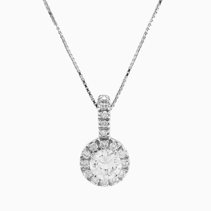 The pendant made in 18k white gold, features 0.82ct with the beautiful round cut central diamond weighing an impressive 0.61ct. The central stone is showcased within a circle of smaller round cut diamonds which also extend up the pendant. Comes with 42 cm chain made in 18k white gold.