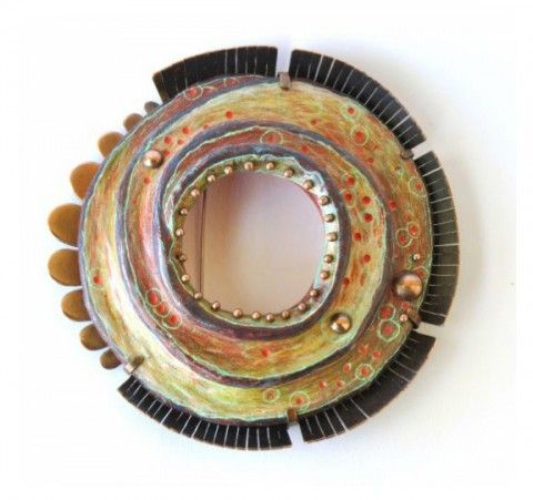 Annie Pennington mixes together fiber, metals, colored pencils and more with her polymer clay jewelry, as seen on The Polymer Arts blog, http://www.thepolymerarts.com/blog/9335