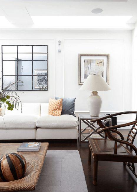 Framed Mirror Above White Couch - Use the mirror both to reflect light and to add character to the room