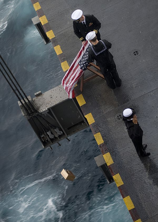 Sailors commit a Sailor's remains to the sea during a burial at sea ceremony aboard the aircraft carrier USS Harry S. Truman (CVN 75).