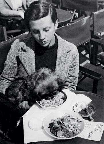 Photographer Gerda Taro with a dog at a Paris cafe, 1935/36.