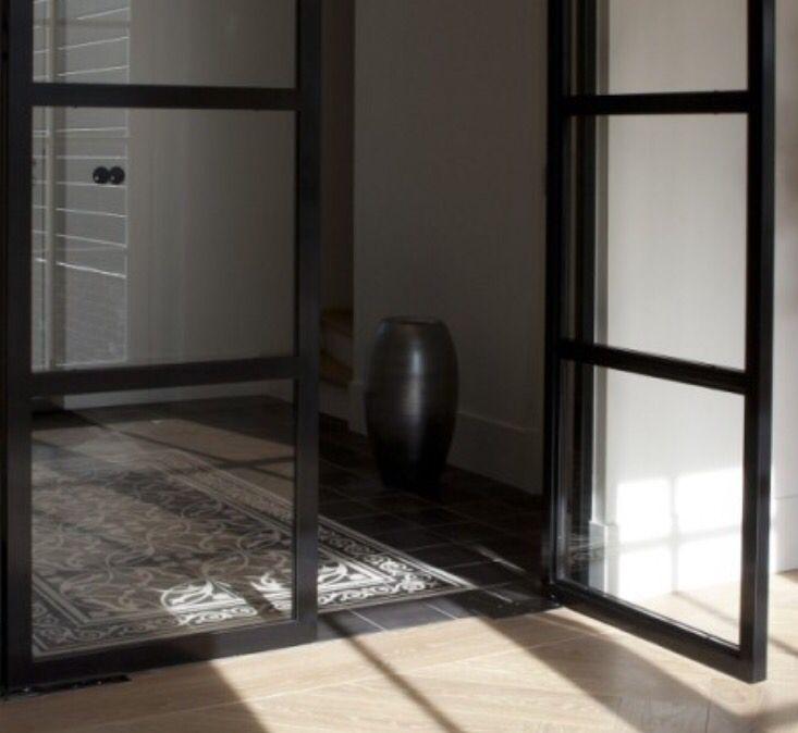 Strakke overgang tussen Portugese tegels en houten vloer door platte drempel. Ruimtelijke maar toch sfeervolle en verrassende doorkijk.