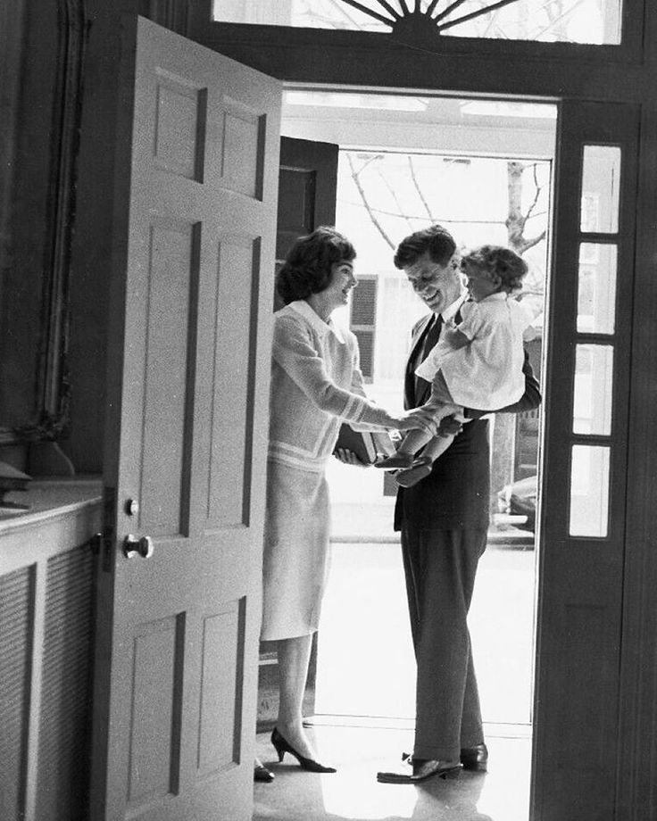 Jacqueline and Caroline Kennedy say goodbye to Senator John Kennedy in their Georgetown home as he heads off to his office in the Senate, 1959