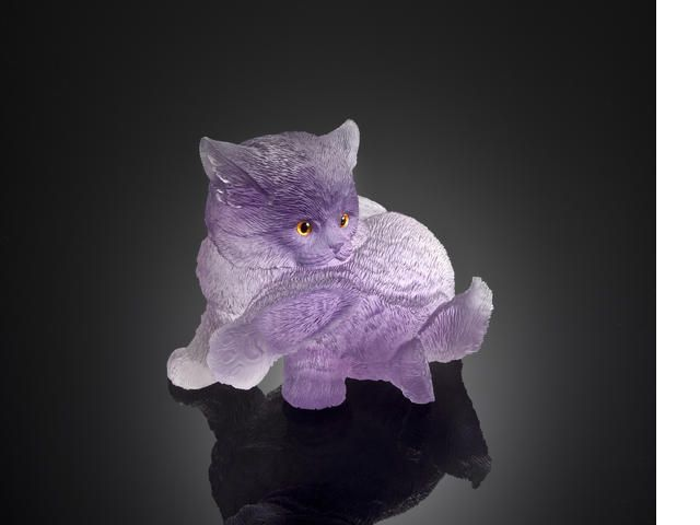 Amethyst Carving of a Kitten Alfred Zimmerman Idar-Oberstein, Germany  Depicting a kitten grooming his leg, carved from a single large crystal of fine transparent violet amethyst, realistically textured to suggest the fur. Weighing approximately 1135 carats. Length 3 1/4 in.
