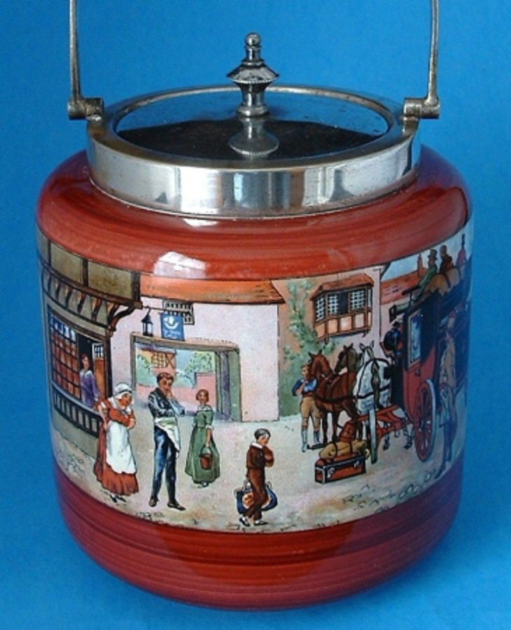This is an antique biscuit barrel, biscuit jar or cookie jar made in the 1920s by Lancaster and Sandland, England. The ceramic biscuit jar has a neat all around design of a victorian scene centering a