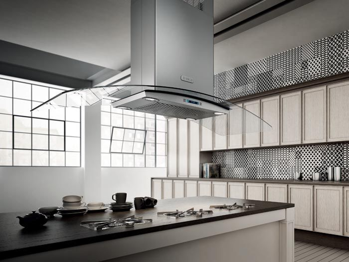 """CINGOLI - Designed to be suspended above a kitchen island, this hood takes flight with graceful 36"""" or 42"""" arched glass wings, which allow natural light to illuminate the surface below."""